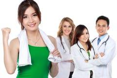 Vrouwenoefening en haar team van arts bij de achtergrond stock afbeeldingen