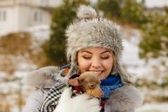 Vrouwenomhelzing die haar verwarmen weinig hond in de winter stock afbeelding