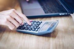 Vrouwenondernemer die een calculator gebruiken aan het berekenen financieel uitgaven thuis bureau royalty-vrije stock fotografie