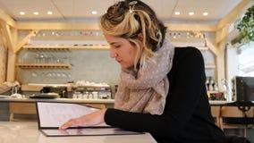Vrouwenonderzoek naar opties op menu in een restaurant stock video