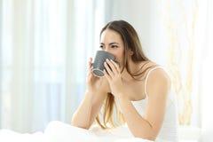 Vrouwenontwaken het drinken koffie op een bed royalty-vrije stock foto's