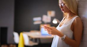 Vrouwenontwerper die op mobiele telefoon in bureau gebruiken Stock Afbeelding