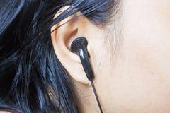 Vrouwenoor met zwarte oortelefoon, Zwarte oortelefoon in het oor van het meisje Royalty-vrije Stock Foto's