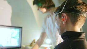 Vrouwenoptometrist die jongens` s ogen in oftalmologiekliniek onderzoeken - schuif stock footage
