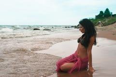 Vrouwenplaatsing op zand dichtbij het overzees Royalty-vrije Stock Afbeeldingen
