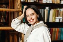 Vrouwenportret dichtbij de Boekenrekken stock fotografie