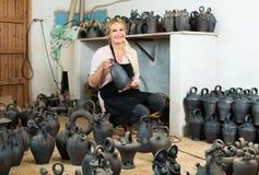 Vrouwenpottenbakker die zwarte verglaasde keramiekschepen in studio houden stock foto