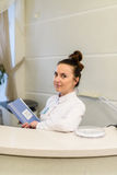Vrouwenreceptionnist in medische laagtribunes bij ontvangstbureau Royalty-vrije Stock Afbeeldingen