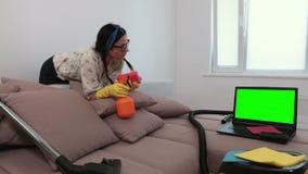 Vrouwenreinigingsmachine dichtbij bank het letten op laptop met het groene scherm stock video