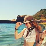 Vrouwenreiziger die dichtbij het overzeese strand, glimlachend en mooi, gekleed in boho elegante armbanden en hoed wandelen, stock afbeelding