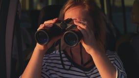 Vrouwenreiziger die door verrekijkers van een autoraam kijken stock video