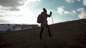 Vrouwenreiziger die met Rugzak in Bergen wandelen Silhouetwandelaar die in de bergen, de vrijheid en het geluk lopen stock videobeelden