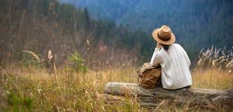 Vrouwenreiziger die met rugzak van zonsondergang op piek van berg genieten royalty-vrije stock afbeeldingen