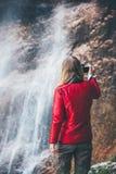 Vrouwenreiziger die waterval van mening genieten Stock Foto