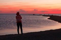Vrouwenreiziger gebruikend smartphone en nemend foto van kleurrijke overzeese zonsondergang Royalty-vrije Stock Foto