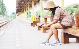 Vrouwenreiziger het spelen smartphone tijdens het wachten trein bij platform royalty-vrije stock foto's