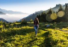 Vrouwenreiziger met de hoed van de rugzakholding en het bekijken verbazend bergen en bos, het concept van de zwerflustreis, ruimt Stock Foto's