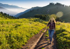 Vrouwenreiziger met de hoed van de rugzakholding en het bekijken verbazend bergen en bos, het concept van de zwerflustreis, ruimt Stock Afbeeldingen