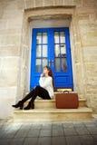 Vrouwenreiziger met een kofferzitting dromerig bij haar huis Stock Afbeeldingen