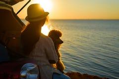 Vrouwenreiziger met hondzitting in autoboomstam dichtbij overzees, het letten op zonsondergang royalty-vrije stock fotografie