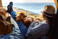 Vrouwenreiziger met hondzitting in autoboomstam dichtbij overzees, het letten op zonsondergang royalty-vrije stock afbeeldingen
