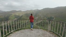 Vrouwenreiziger op observatieplatform de mening van de bergvallei met een kloof, bergpieken stock footage