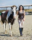 Vrouwenruiter die met paard op renbaan loopt Stock Afbeeldingen