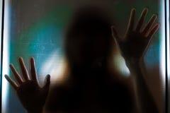 Vrouwenschaduw achter doorzichtige spiegel Stock Foto