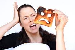 Vrouwenschreeuw bij een gebrande plak van toost royalty-vrije stock afbeeldingen