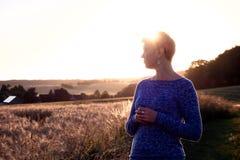 Vrouwensilhouet bij zonsondergang tegen de zon en een graangebied op de achtergrond Stock Foto's