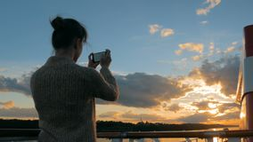 Vrouwensilhouet die foto van zonsondergang met smartphone op dek van cruiseschip nemen stock video