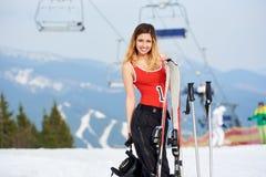 Vrouwenskiër op de bovenkant van de sneeuwheuvel met skis bij skitoevlucht Stock Foto's