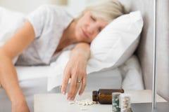 Vrouwenslaap in bed met pillen in voorgrond Stock Afbeeldingen