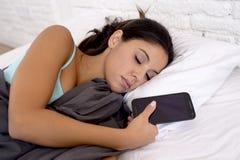 Vrouwenslaap in bed thuis samen met mobiele telefoon in Internet-netwerkverslaving royalty-vrije stock fotografie