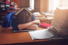 Vrouwenslaap met een boek op haar hoofd Royalty-vrije Stock Afbeelding