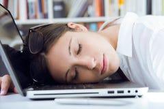 Vrouwenslaap op haar laptop in de werkplaats royalty-vrije stock foto