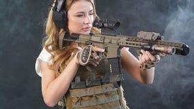 Vrouwensluipschutter met sluipschuttergeweer Wijfje in Legermilitair met machinegeweer Langzame Motie stock footage
