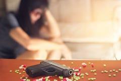Vrouwenspanning en gedeprimeerd van haar ziekte, besliste zij met een kanon te doden Stock Foto