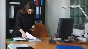 Vrouwenspion op de telefoon die beelden van geheime dossiers in het bureau nemen stock footage
