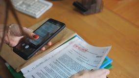 Vrouwenspion op de telefoon die beelden van geheime dossiers in het bureau nemen stock video