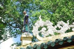 Vrouwenstandbeeld op het dak van een tempel Stock Foto