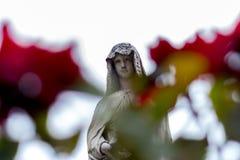 Vrouwenstandbeeld in Recoleta-Begraafplaats met twee rozen op de voorgrond stock fotografie