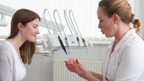 Vrouwentandarts die met vrouwelijke patiënt in kliniek spreken Vrouwelijke professionele arts op het werk Tand controle omhoog stock videobeelden