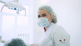 Vrouwentandarts op kantoor Een vrouwelijke artsentandarts werkt aan de kaak en de tanden van een mannelijke patiënt bekijkt de ca stock videobeelden