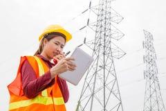 Vrouwentechniek die aan toren Met hoog voltage werken Royalty-vrije Stock Afbeeldingen