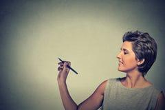 Vrouwentekening die aan boord met lege exemplaarruimte schrijven royalty-vrije stock afbeeldingen