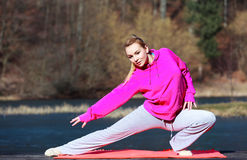 Vrouwentiener in bovenkledij die oefening op pijler doen openlucht stock afbeelding