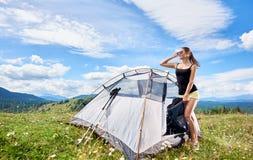 Vrouwentoerist die in bergsleep wandelen, die de zomer van zonnige ochtend in bergen genieten dichtbij tent royalty-vrije stock foto's