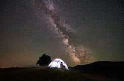 Vrouwentoerist die bij nacht rusten die onder sterrige hemel en Melkachtige manier kamperen stock fotografie