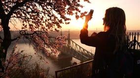 Vrouwentoerist die foto op een mobiele telefoon nemen cityscape en de Vrijheidsbrug over Donau van het terras van stock video